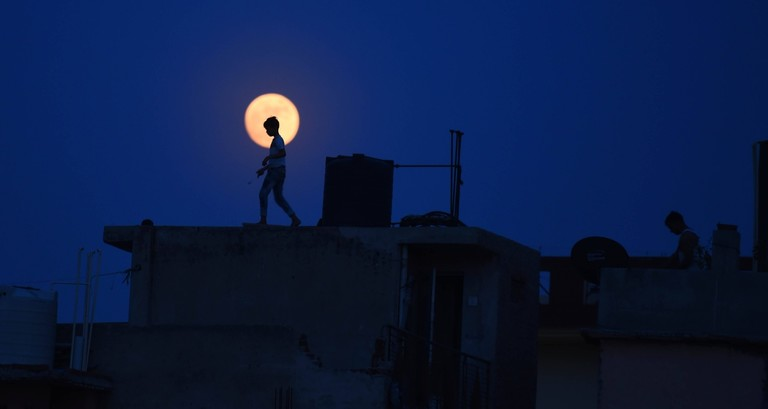 A boy seen against the backdrop of a full moon, on July 4, 2020 in New Delhi, India.