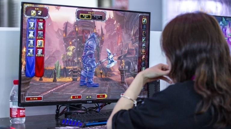 Eine Frau sitzt in Shanghai vor einem PC und spielt ein Online-Game.