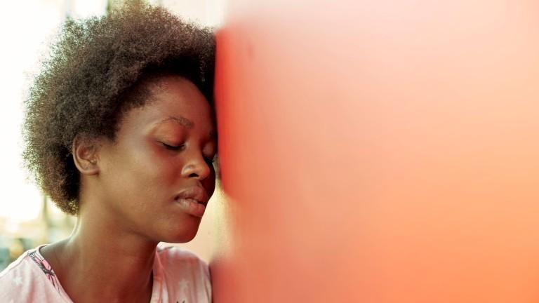 Junge Frau lehnt ihren Kopf gegen eine Wand.