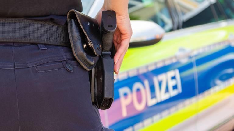 Polizistin mit Waffe und Dienstwagen