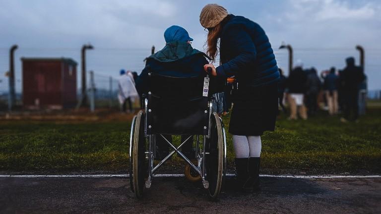 Eine junge Person im Rollstuhl mit einer Assistenz