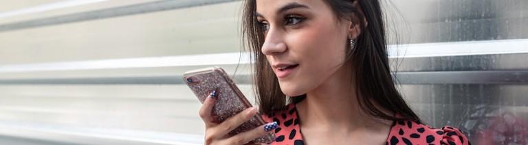 Eine Jugendliche spricht eine Sprachnachricht auf ihrem Handy ein.