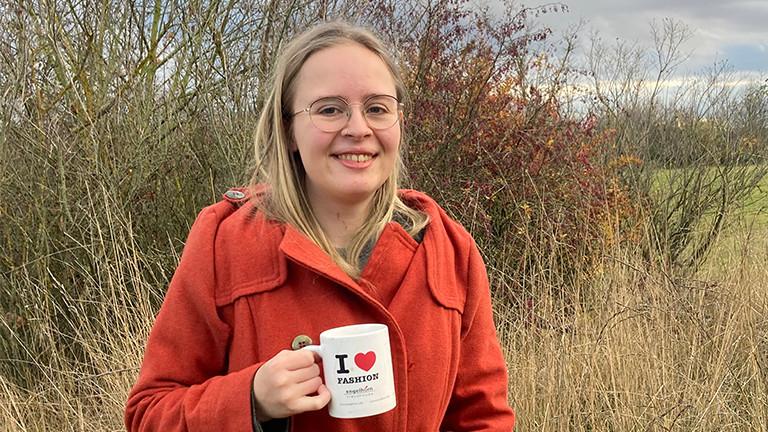 Eine Frau mit langen blonden Haaren steht in einem rotem Mantel vor einer herbstlichen Landschaft