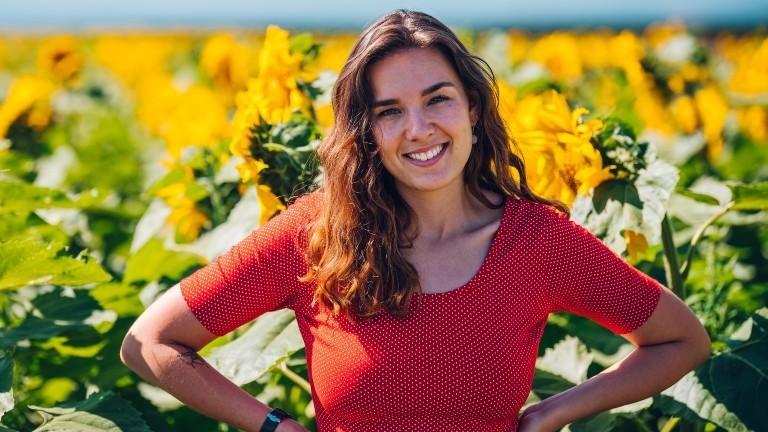 Tanja steht vor einem Feld voller Sonnenblumen.