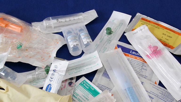 Medizinprodukte in Plastikverpackungen vor blauem Hintergrund.