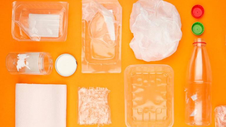 Durchsichtige Plastikverpackungen vor orangem Hintergrund.