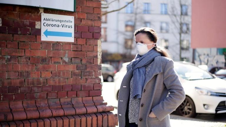 Junge Frau mit Mund-und Nasenschutz geht zu einer Corona-Test-Stelle.