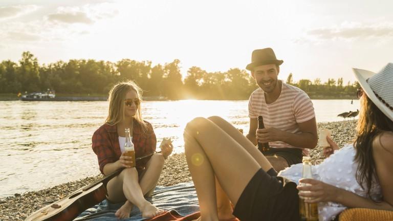 Junge Menschen feiern an einem Fluss.