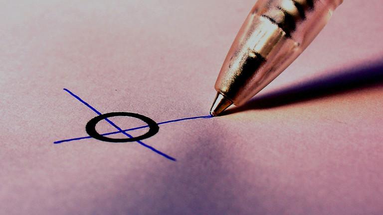 Ein Stift macht ein Kreuzchen in einem Kreis.