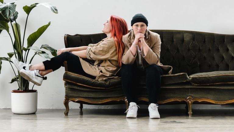 Marie (l.) und Julie (r.) sitzen auf einem Sofa.