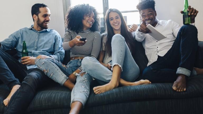 Junge Menschen sitzen auf dem Sofa und schauen TV.