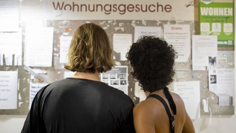 Zwei junge Menschen stehen vor einem Aushang mit Wohnungsgesuchen.