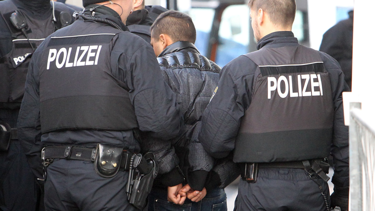 Polizisten begleiten einen straffällig gewordenen Asylbewerber in Handfesseln auf dem Flughafen