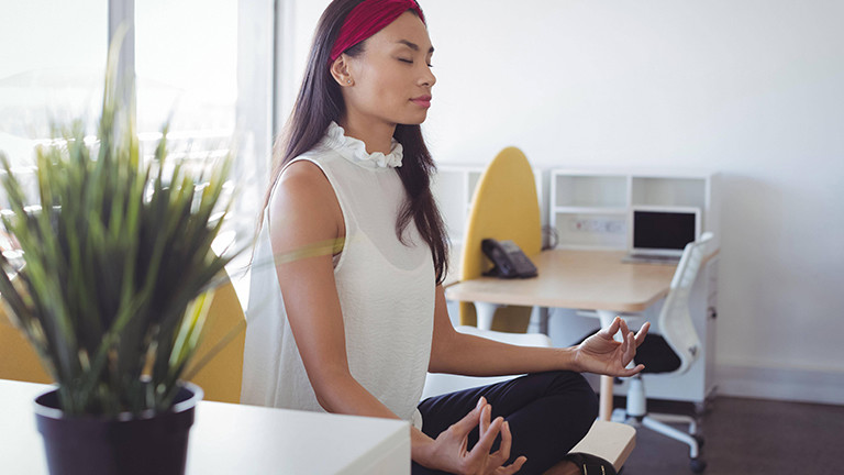 Frau, die im Büro meditiert