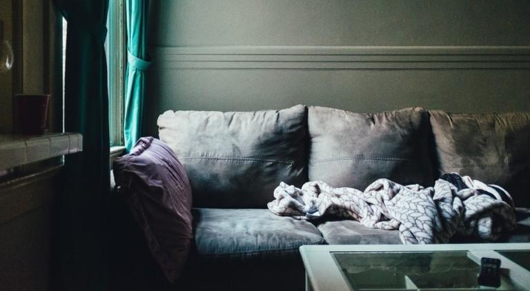 Eine leere Couch mit einer Decke drauf