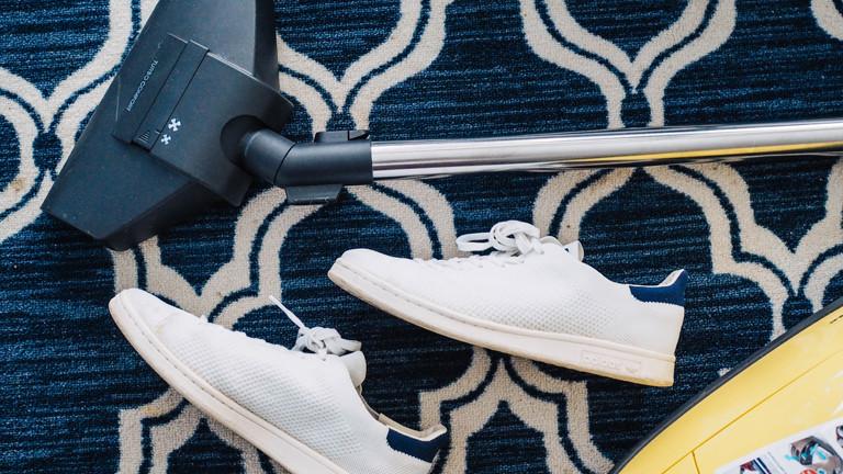 Ein Staubsauger und Schuhe auf einem Teppichboden