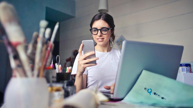 Eine Frau sitzt vor ihrem Laptop, im Vordergrund sind auch Pinsel zu sehen