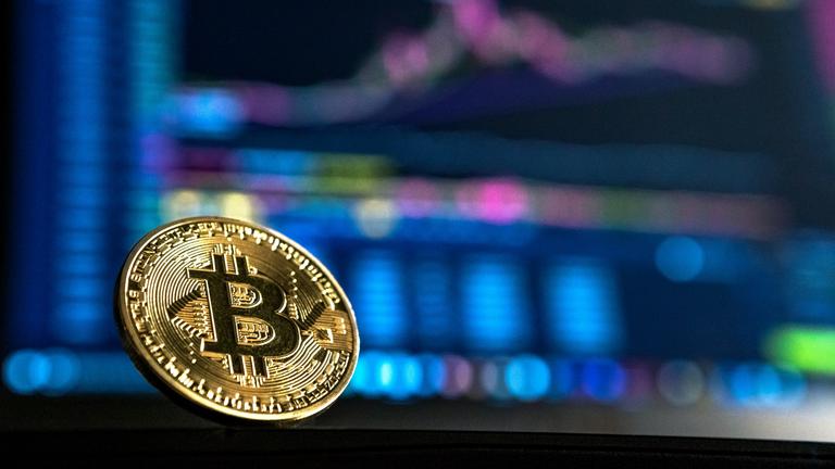 Bitcoin Münze vor verschwommenem, buntem Bildschirm