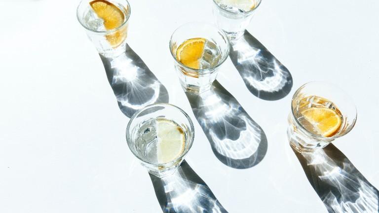 Ein paar Gläser mit Wasser werfen Schatten auf einen Tisch