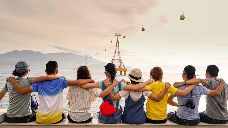 Freunde sitzen auf einer Mauer und legen sich dabei die Arme auf die Schultern.