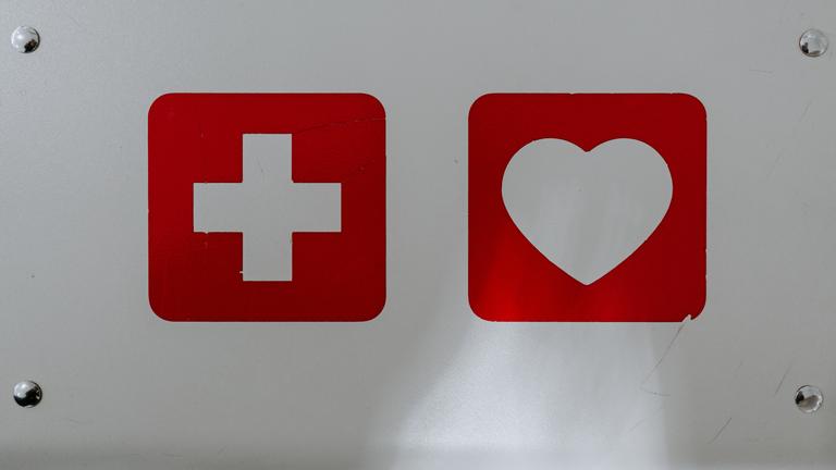 Ein Kreuz und ein Herz vor rotem Hintergrund