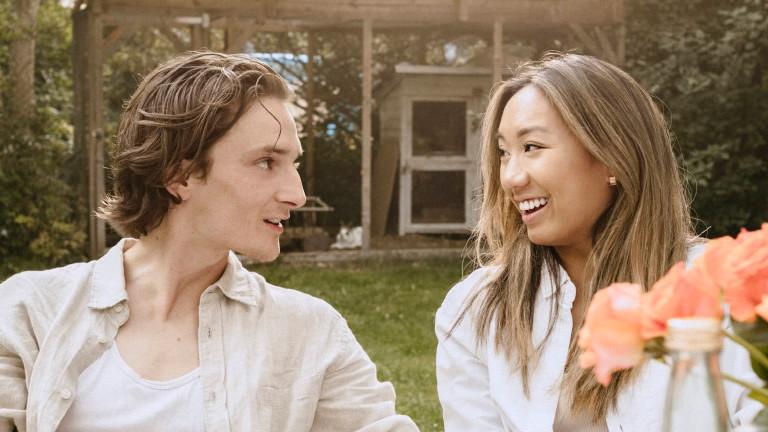 Eine junge Frau und ein junger Mann unterhalten sich in einem Garten