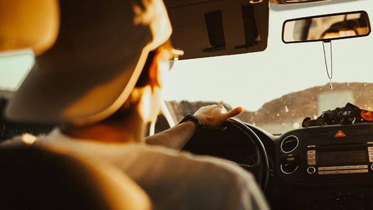 Ein Mann sitzt am Steuer eines Autos.