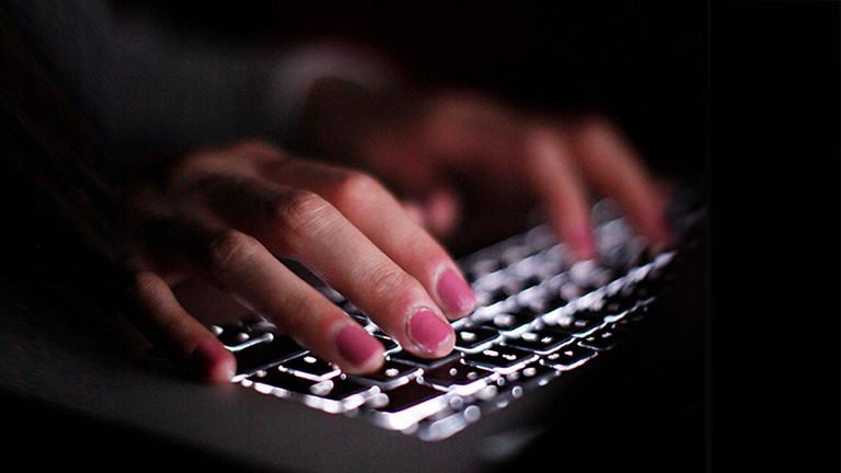 Frauenhände tippen im Dunkel auf einer Tastatur