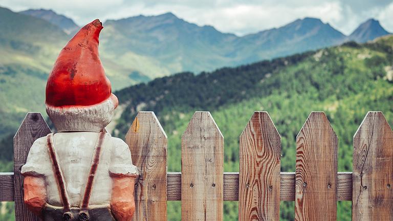 Ein Gartenzwerg steht am Lattenzaun und schaut auf die Berge.