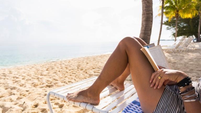 Eine Frau liegt am Strand und liest ein Buch