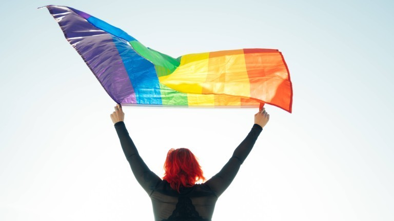Eine Frau weht eine Regenbogenflagge