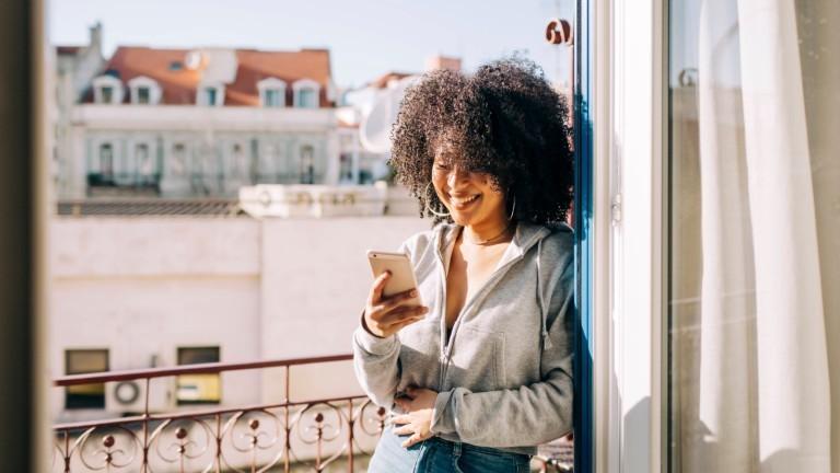Eine junge Frau lacht in ihr Handy rein