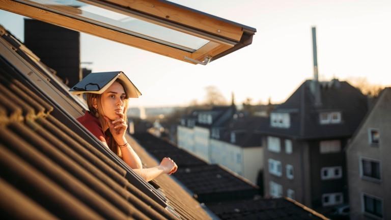 Eine Frau mit einem Buch auf dem Kopf schaut denkend aus dem Fenster