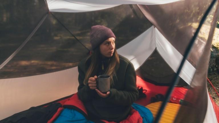 Ein Mädchen sitzt alleine in einem Zelt
