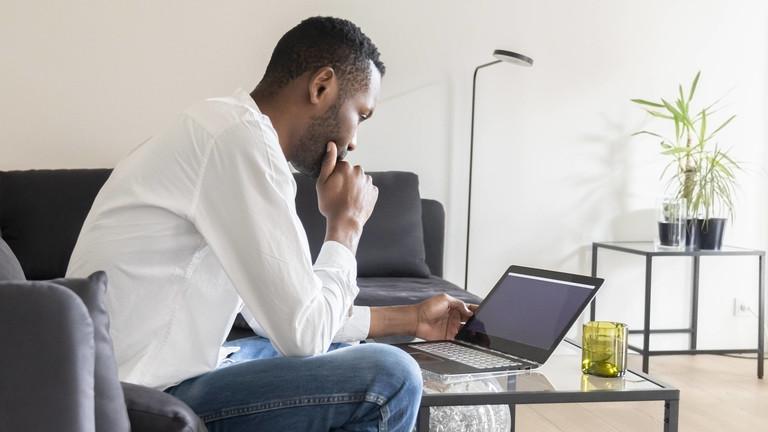 Ein Mann schaut konzentriert auf seinen Laptop