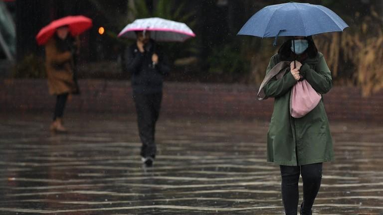 Menschen mit Maske und Regenschirm laufen im Regen