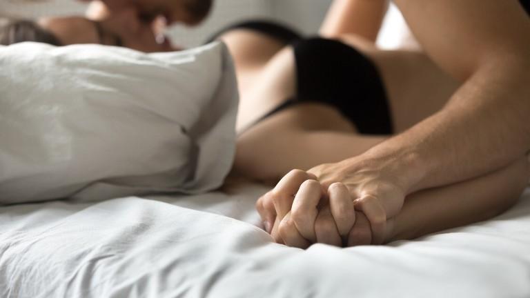 Eine Frau und ein Mann haben Sex in einem Bett