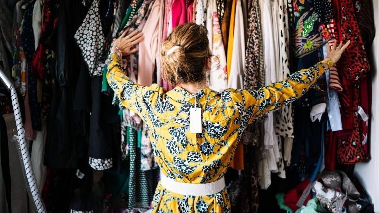 Eine Frau mit Etikett an ihrem Kleid schaut in ihren Kleiderschrank