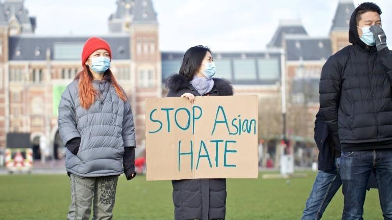 Zwei Asiatinnen und ein Asiate demonstrieren in Amsterdam