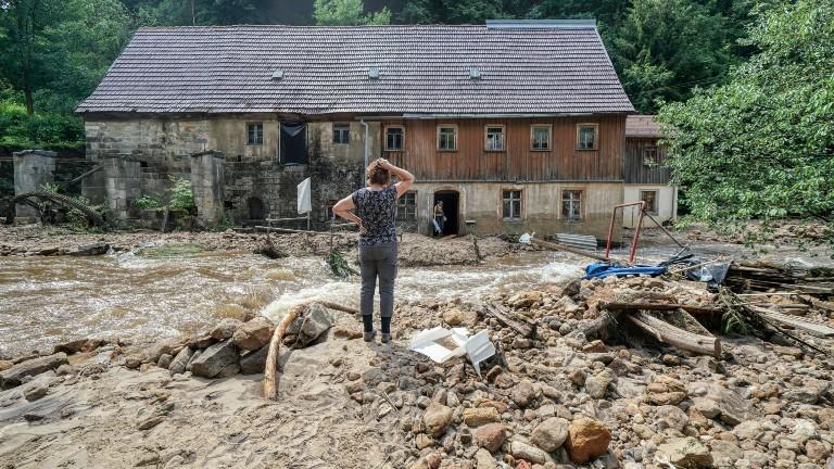 Eine Frau steht verzweifelt vor ihrem zerstörten Haus