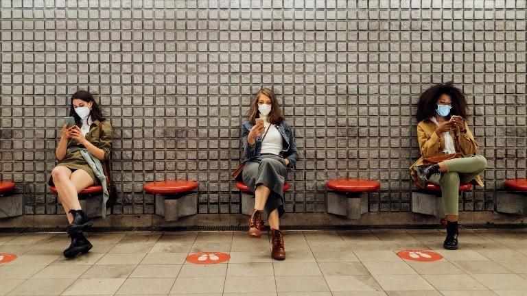 Drei Frauen sitzen an ihrem Handy mit Abstand und Maske