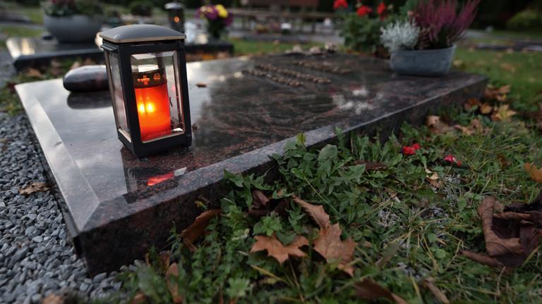 Ein Grab mit rotem Grablicht