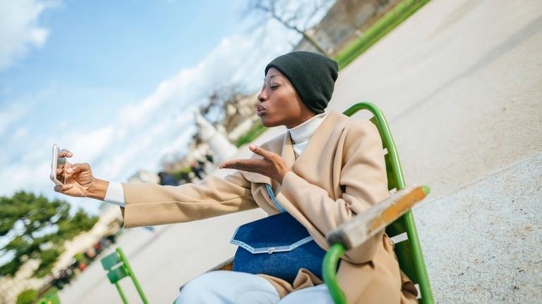Frau sitzt auf einem grünen Stuhl und macht einen Handkuss in ihre Smartphone-Kamera
