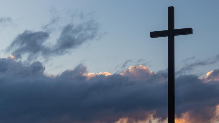 Ein schwarzes Kreuz, im Hintergrund Wolken im Abendlicht