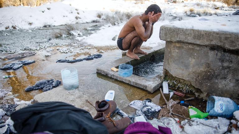 Hagiaz Abdulrehman wäscht sich in eisiger Kälte im Geflüchteten-Camp in der Nähe von Bihac, Bosnien-Herzegovina, 15.1.2021.