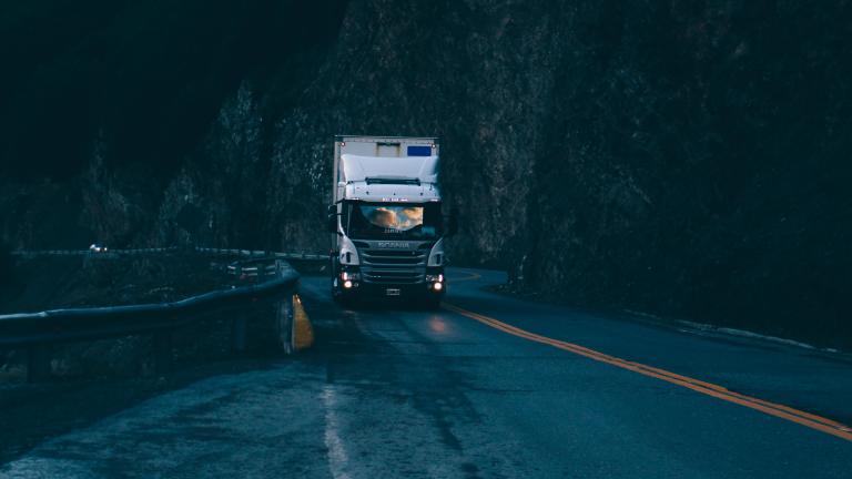 Ein LKW fährt im Halbdunkel durch eine Kurve
