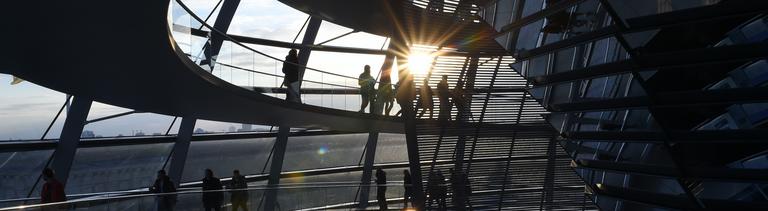 Kuppel des Reichstagsgebäudes in der Abendsonne mit Menschen