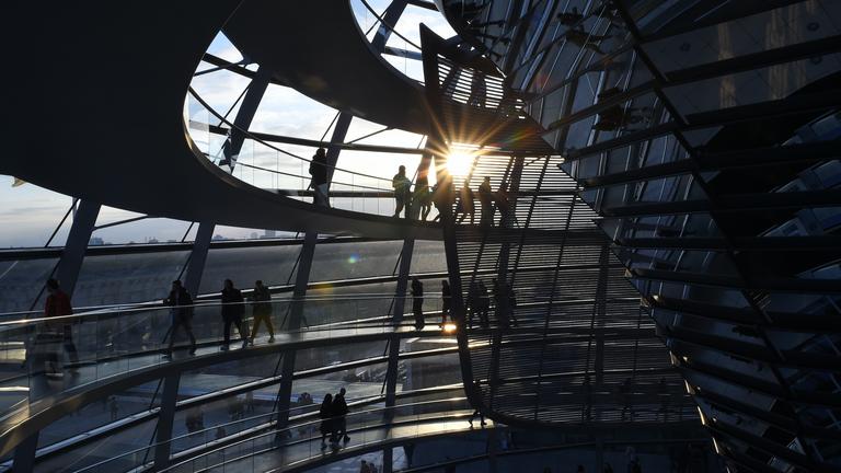 Kuppel des Bundestags in der Abendsonne mit Menschen