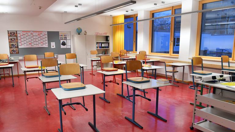 In einem Klassenzimmer stehen die Stühle auf den Tischen