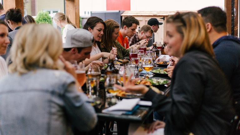 Freunde sitzen an einem Tisch und essen